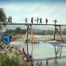 Photograph of farmers crossing a river on a wooden bridge