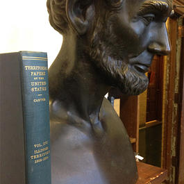Photograph of bust of Abraham Lincoln with volume of territorial papers